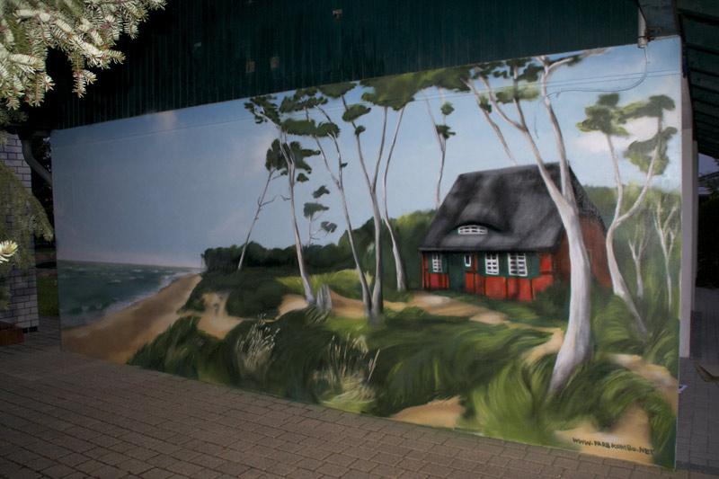 Graffiti-Sprayer Mecklenburg Vorpommern gestaltet Außenfassade bei Godewind Ferienwohnungen mit Ostseeküste als Bildmotiv.