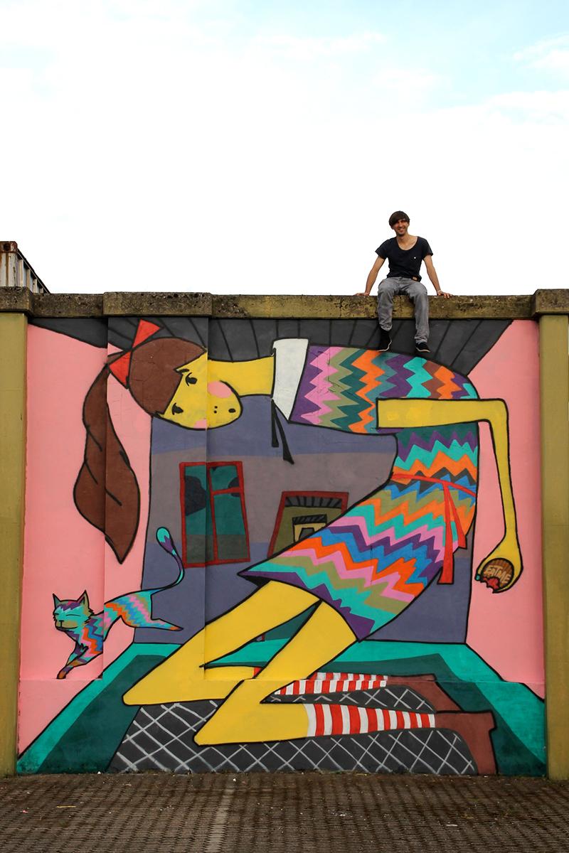 Illustration von Alice im Wunderland im Format 4m x 5m im Luisenviertel. Alice hat ein bunt gestreiftes Kleid an und eine rote Schleife im Haar. Sie ist am wachsen und stößt bereits mit dem Rücken gegen die Decke des farbenfrohen Zimmers an. Neben Alice springt ein bunte Katze. Der Graffiti-Künstler sitzt auf der bemalten Mauer.