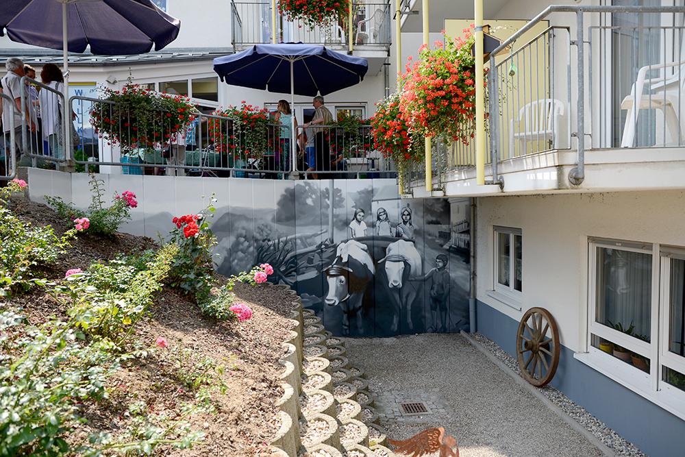 GRAFFITI-KÜNSTLER ODENWALD: Blick auf die fertige Wand von der Terrasse des Seniorenzentrums aus. Malerische Umsetzung einer Straße in Limbach Anfang des zwanzigsten Jahrhunderts.