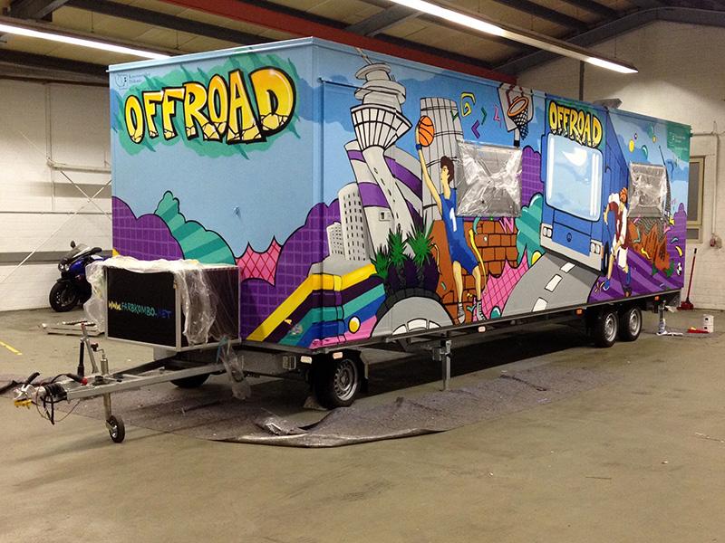 Graffitisprayer gestaltet in Düsseldorf das mobile Jugendzentrum mit einer farbenfrohen Illustration, die auf einen Anhänger sprüht worden ist.