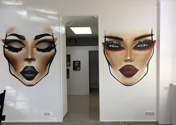Graffitisprayer Düsseldorf: Gesichter gesprüht an einer Wand im Make-up-Studio
